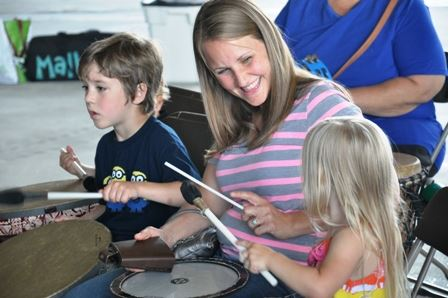 mom and two children bang a drum during summer reading program