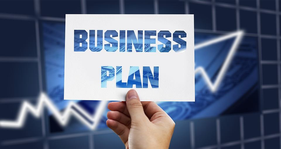 "Picture of a person holding a card that reads: ""BUSINESS PLAN"""
